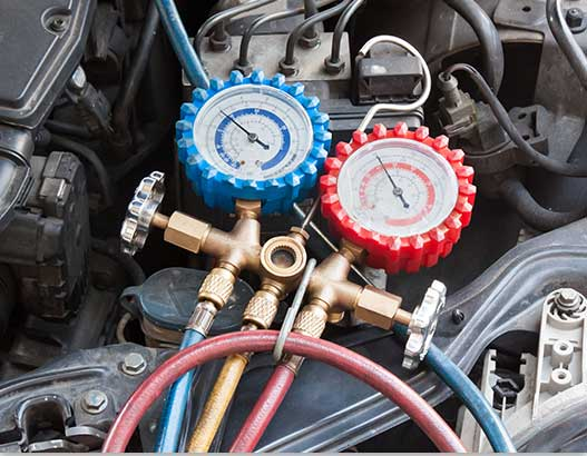 Auto Mechanic at G & G Automotive checking engines gauges
